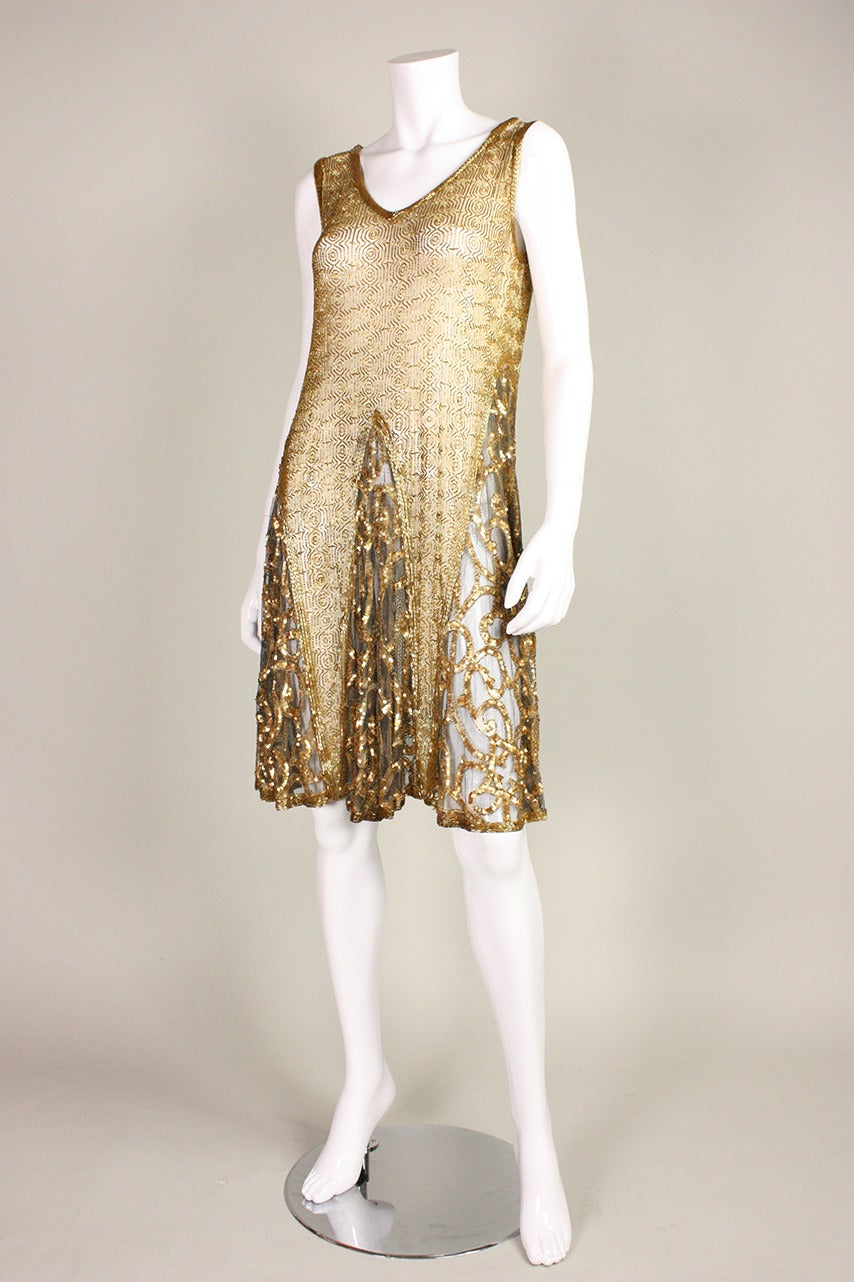 Vintage dress dates to the Art Deco era during the Roaring 1920's.  It is made of soft sheer netting that is covered with gold bugle beads arranged in a geometric pattern.  Godets in skirt have scrolling bands of gold sequins.  Unlined.  No