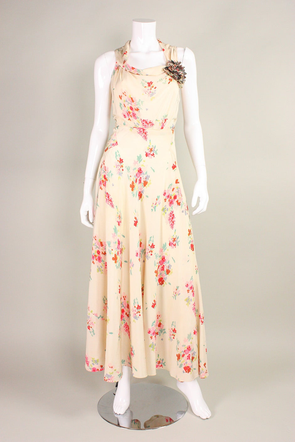 """Vintage gown dates to the 1930's and retailed at """"Stefan Kozak Inc."""" in New York City.  It is made of textured silk crepe with a multicolor floral print. It is cut on the bias, which creates a very flattering shape. Front and back cowl"""