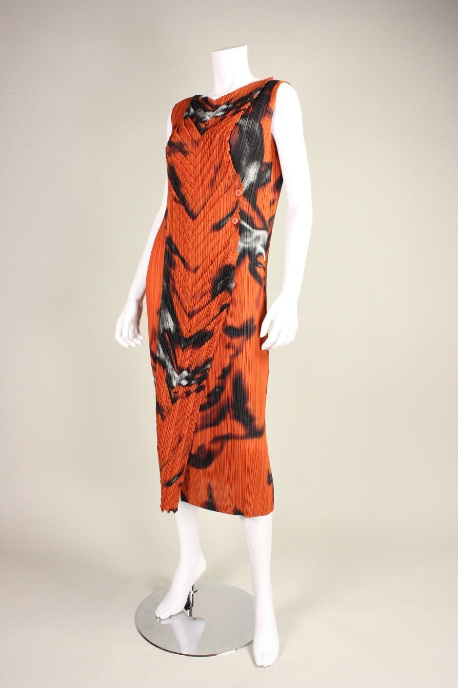 Striking dress from Issey Miyake's Fete line is made of orange fabric that is permanently pleated with an almost ghostly abstract print in black and white.  Contrasting pleats in a chevron pattern run vertically down the center front.  Side button