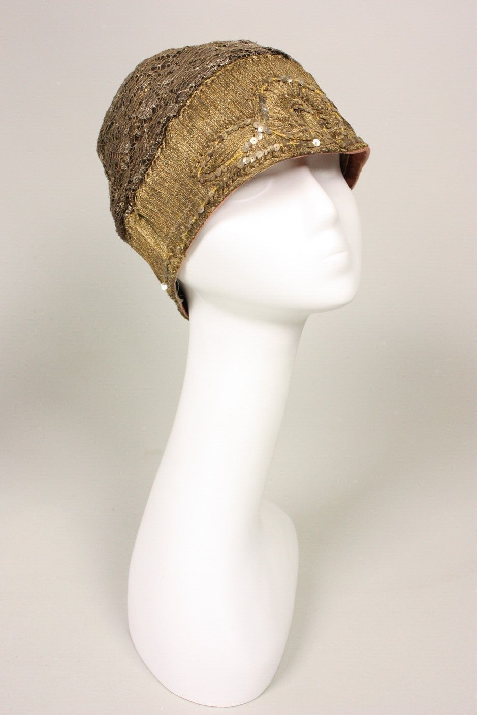 Vintage cloche dates to the 1920's and is made of gold lace and bullion that is highlighted with sequins.  Lined.