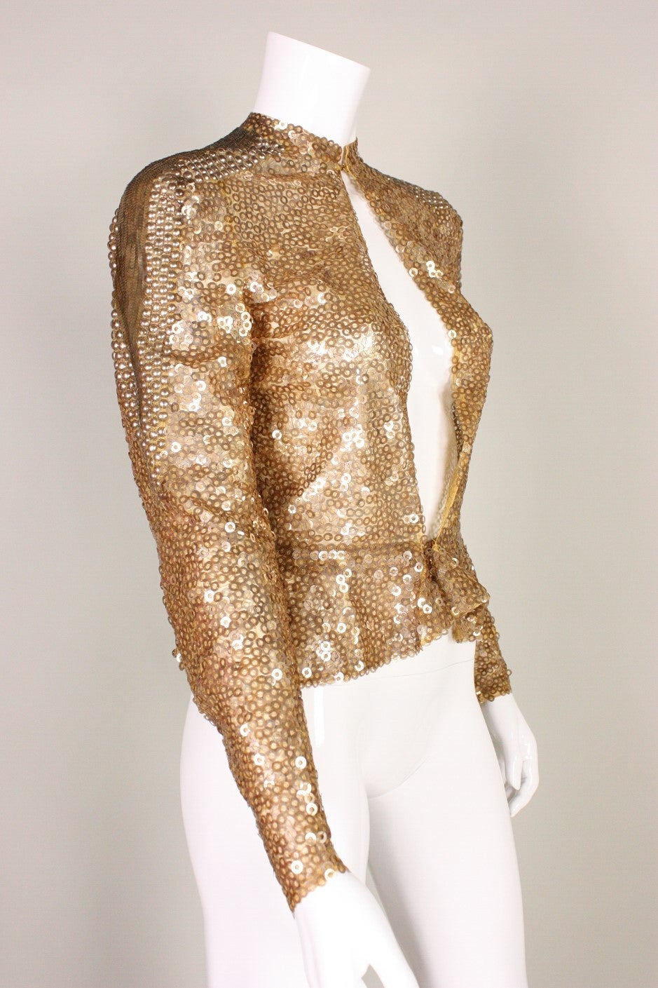 "Vintage jacket dates to the 1930's and is made of gold netting with sparkling gold sequins covering the entirety of the surface.  Center front hook closure at neckline and waist.  Unlined.  Labeled ""Made in France"".