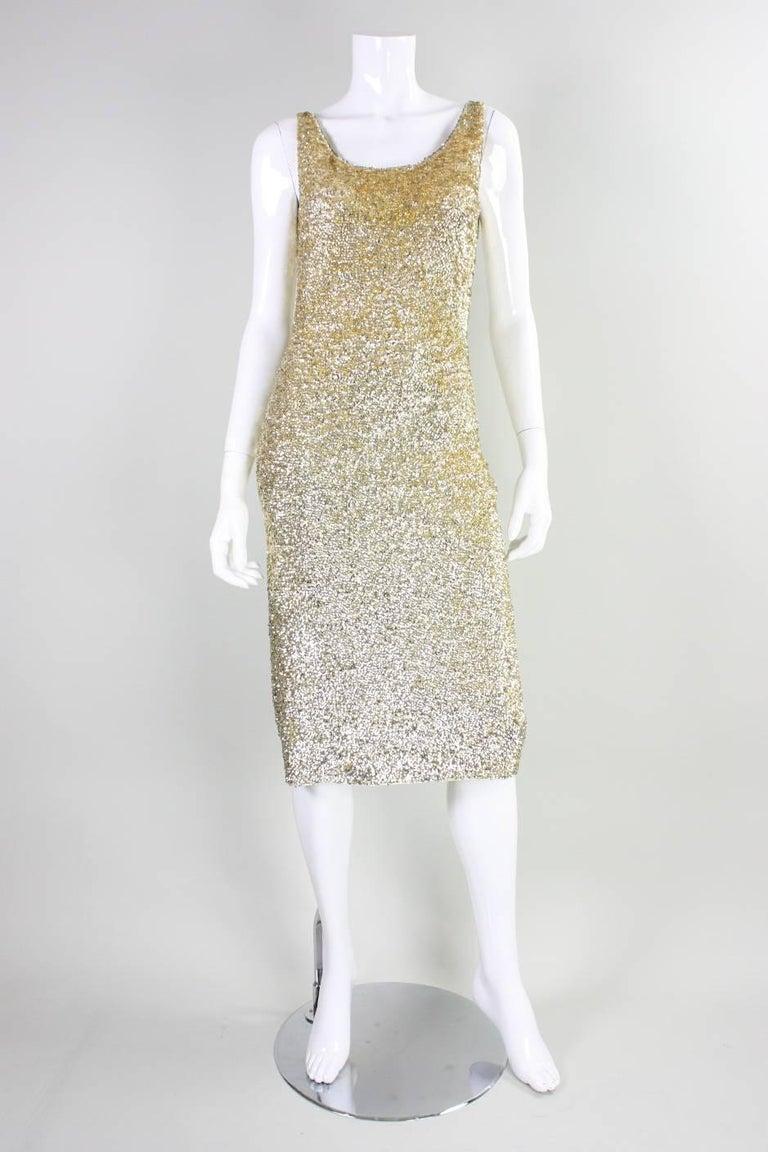 Vintage bombshell cocktail dress from Gene Shelly dates to the 1950's through 1960's.  It is made of ivory wool knit that is densely covered with gold sequins that are hand-sewn onto the knit.  Scoop front and back neck.  Sleeveless.  Completely