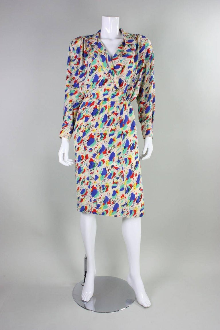 Vintage dress from Chanel is made of off-white silk that features a polychromatic painterly print with cursive Coco written throughout. Crisscrossed bodice has a v-neck, notched lapel, and long sleeves with buttoned cuffs.  Straight skirt has a