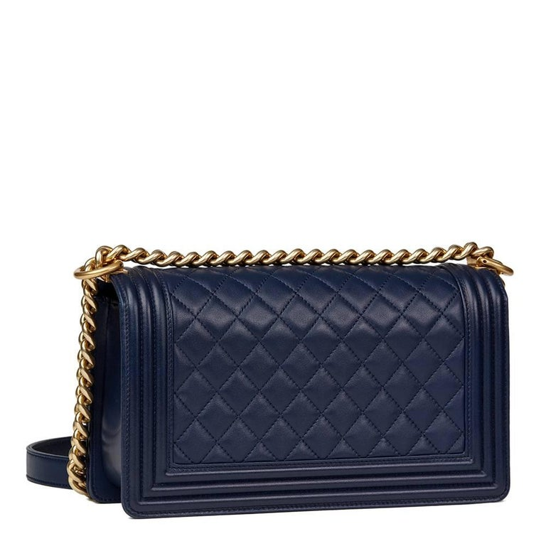 CHANEL Navy Quilted Lambskin Medium Le Boy  This CHANEL Medium Le Boy is in Excellent Pre-Owned Condition accompanied by Chanel Dust Bag, Box, Care Booklet. Circa 2016. Primarily made from Lambskin Leather complimented by Antiqued Gold hardware. Our