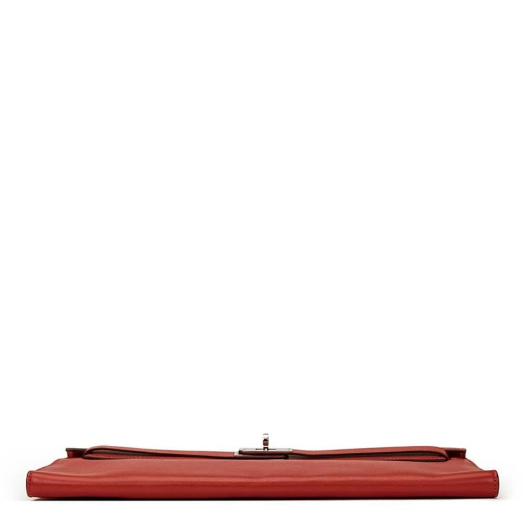 HERMÈS Rouge Garance Swift Leather Kelly Longue Clutch  This HERMÈS Kelly Longue Clutch is in Very Good Pre-Owned Condition accompanied by Hermès Dust Bag. Circa 2007. Primarily made from Swift Leather complimented by Palladium hardware. Our Xupes