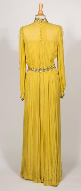 The neckline and the wrists are embroidered With Yellow ,Gold,and Cognac color strass in the shape diamond.