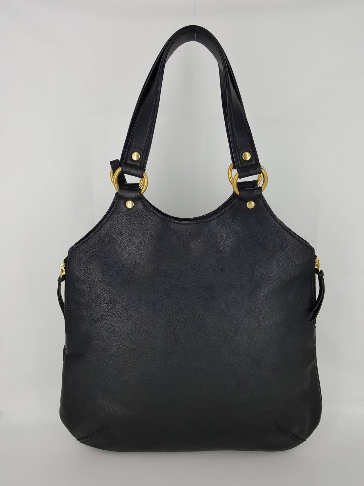 Offered for sale is this black leather YSL Yves Saint Laurent Tribute Bag.  This is done in beautiful black leather and has a YSL Hang tag  logo adornment, dual handles, button closure, and 2 side zippers.  The interior is black satin with 1