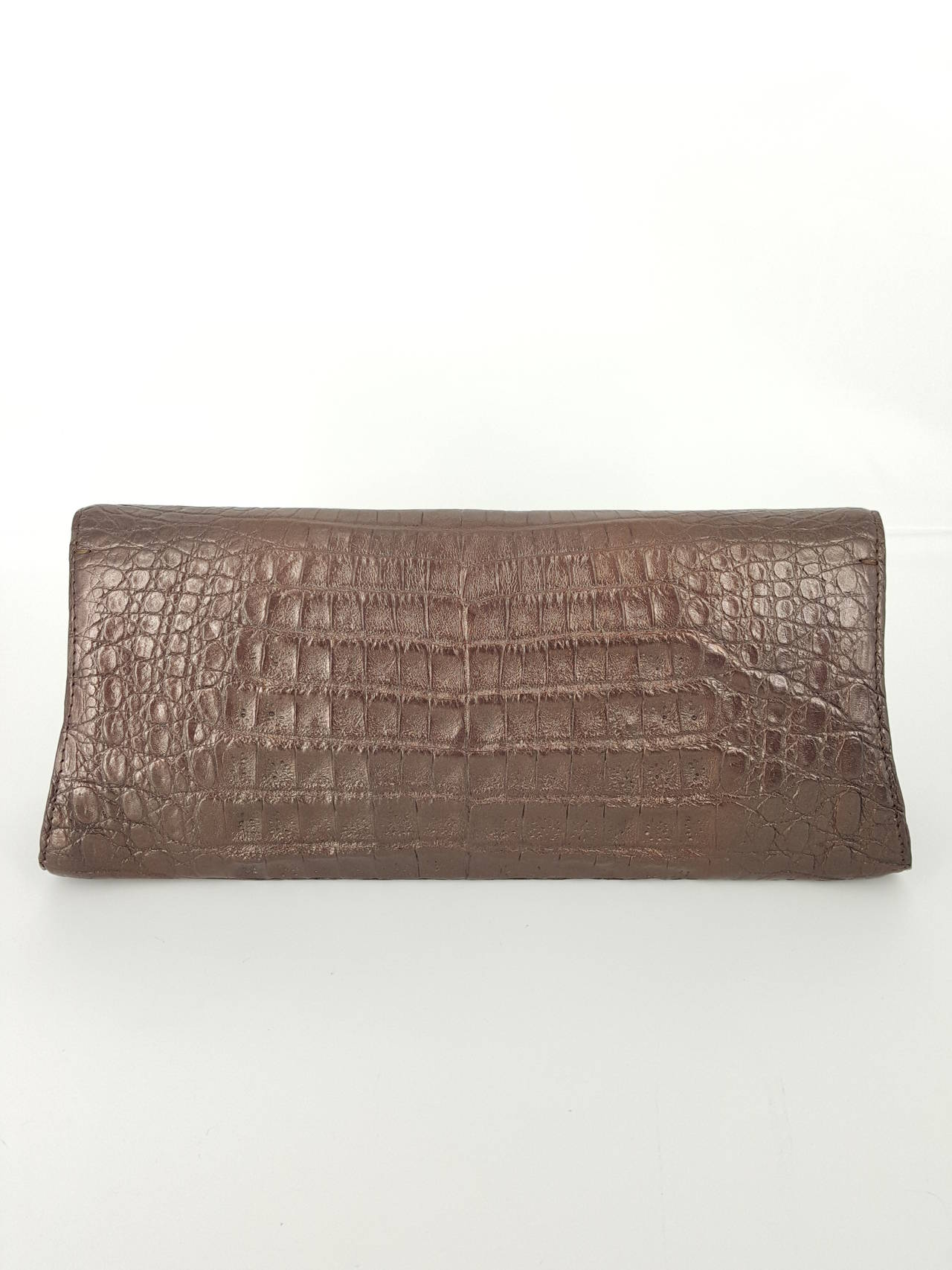 Offered for sale is this Nancy Gonzalez clutch is a shimmery bronze crocodile.