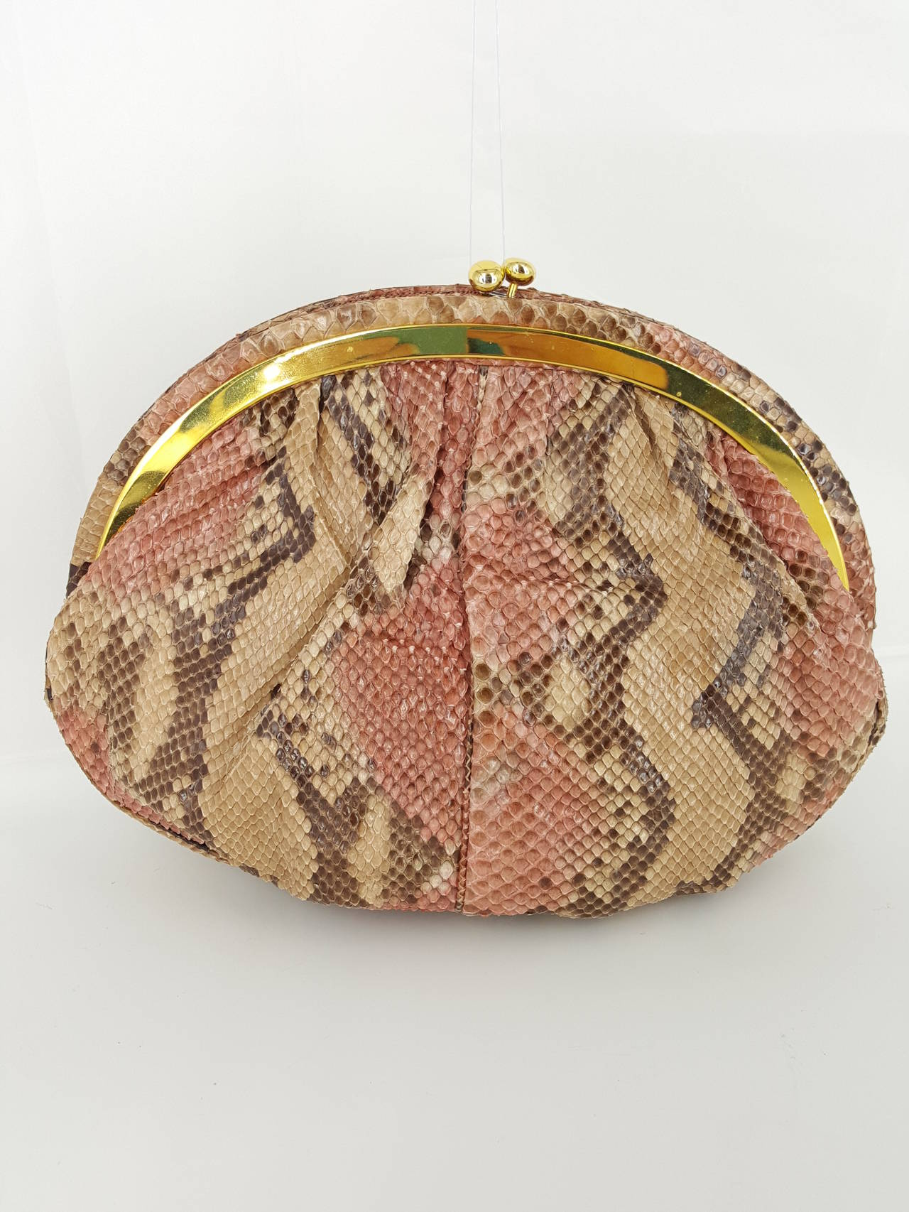 Offered for sale is this lovely large Judith Leiber python clutch/shoulder bag.  The skin is a lovely blend of brown, tan, and soft pink.  The frame is adorned with cabochon red coral and tiger eye.  The metal frame and kiss lock are in gold tone.