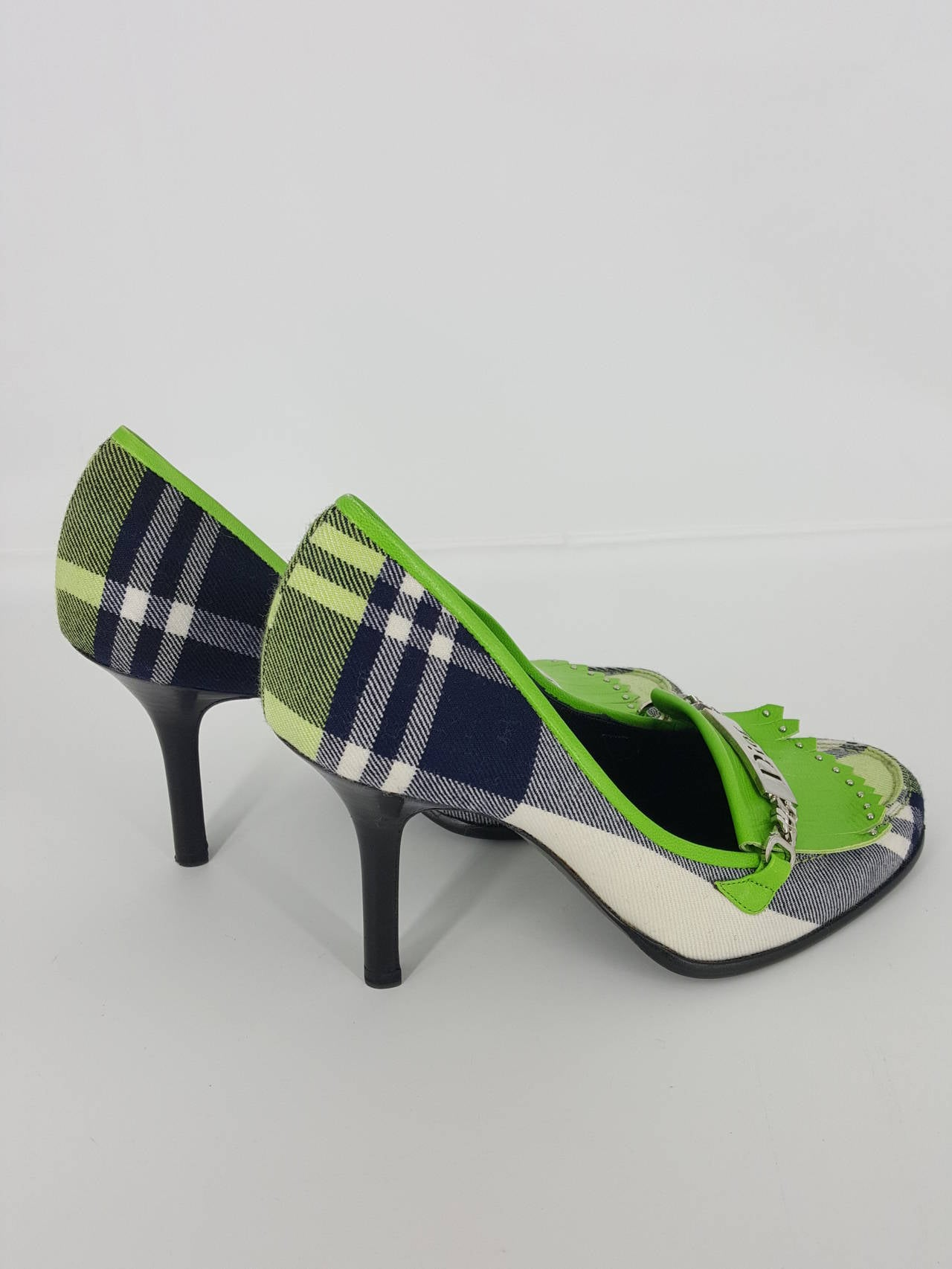 Offered for sale are these new never worn Dior pumps in lime green, navy and white plaid flannel.  They are darling.  The large silver Dior charm on the front and the fringed lime green leather dive it a Scottish flavor.  Great with jeans or  a
