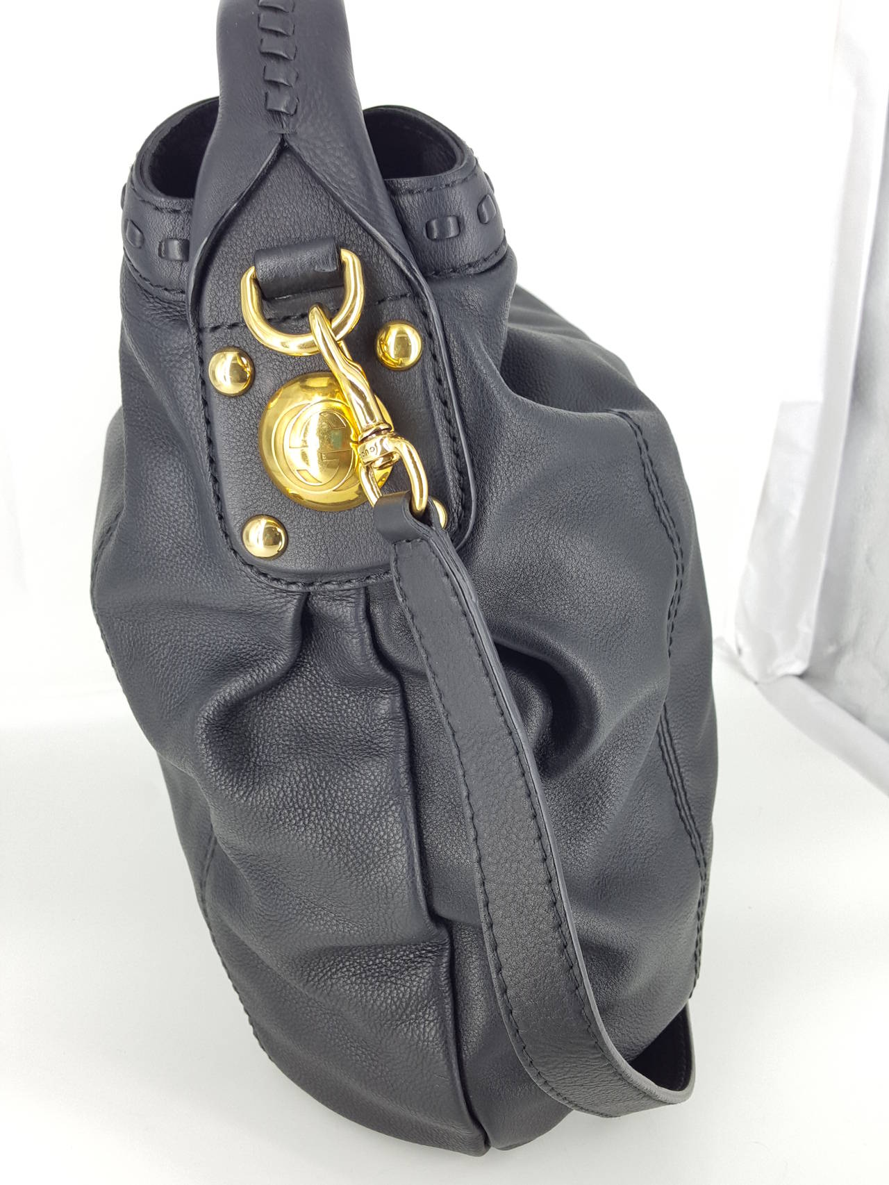 Offered for sale is this Gucci Sunset hobo in beautiful soft black leather,  This bag was in high demand and sold out at Gucci.  It was never carried.   The trim and straps are done with a hand stitched design in the same leather.  The hardware is