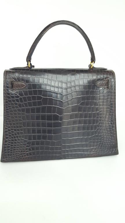 Offered here is a vintage Hermes Kelly 28 cm in a rich dark brown shiny crocodile from 1985.  This bag is in mint condition. The color is so dark it appears black.  All hardware in excellent condition.  will ship with original lock, keys, and dust