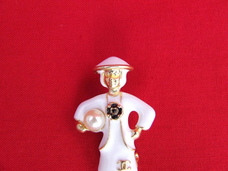 Beautiful Authentic CHANEL Brooch  Made of golden Metal, dress and hat in white Enamel  Represents Mademoiselle Coco Chanel in a white dress, holding a false ivory pearl under her right arm  Black Camelia in the middle, and cc logo in golden metal