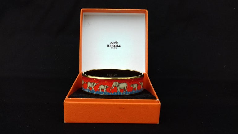 Gorgeous Authentic Hermès Bracelet  Pattern: Elephants Grazing  Hard to find ! One of the most thought after Hermès Bracelet. Rare in red !  Made in Austria + F   Made of printed Enamel and Gold Plated Hardware  Colorways: Red background with yellow