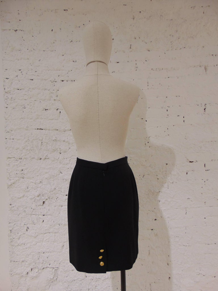 Chanel Boutique black wool skirt  totally made in france in size 40  embellished with 3 gold tone cc logo bottons