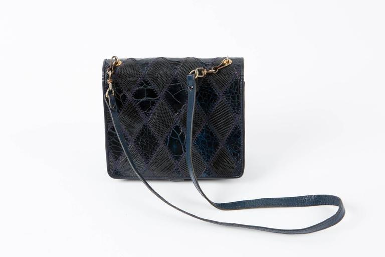 1970s navy leather patches clutch featuring  different leather & reptile parts, four compartments, gold tone metallic opening, a detachable 