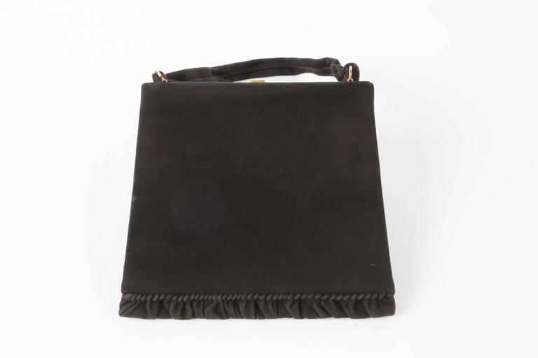 Collector 1950s black suede Delvaux handbag featuring a Cameo clip opening, a flouncy suede bottom finishing, a silk twill lining. Marked: Delvaux Modèle déposé In good vintage condition. Made in Belgium We guarantee you will receive this