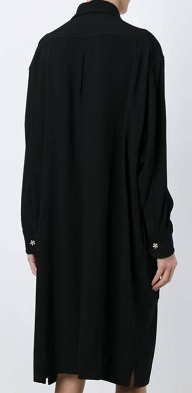 Moschino black wool crepe oversized shirt dress featuring a shirt collar, an oversize volume, front patched pockets, front jewel fancy buttons opening, long sleeves with jewels buttons cuff.