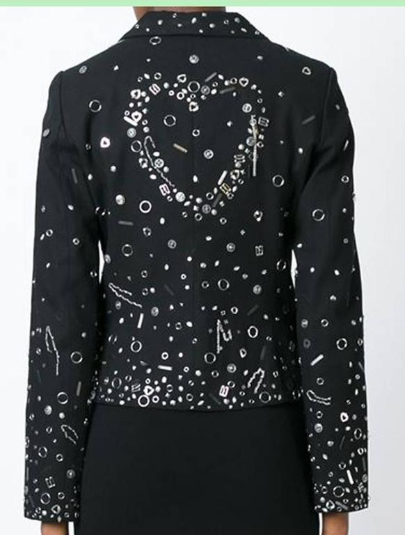 Gorgeous Moschino black stretch cotton embellished blazer featuring notched lapels, a button fastening, flap pockets and long sleeves.  In good vintage condition. Made in Italy. Estimated size: 36FR Chest 35,4in. (90cm) Waist 30,7in (78cm) Sleeve