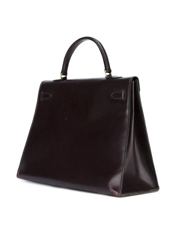 1965-1970s Hermès cherry red box calf leather Kelly tote bag 35cm featuring foldover top with twist-lock closure, a top handle, a trapeze body, plated-gold hardware, an internal slip pocket, a plated-gold SB numbered plaque, and a detachable box