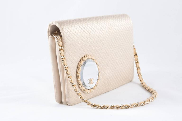 Gorgeous rare Chanel evening satin quilted clutch featuring a silver tone chain twisted with beige leather, (18,1in. (46cm) length) a front round mirror with CC gold tone logo and leather cable with silver tone chain, inside front flap in silk