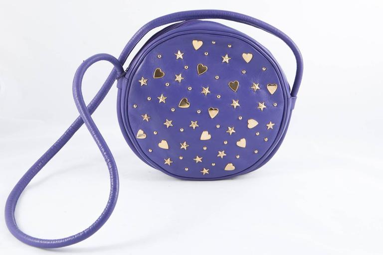 Gorgeous Saint Laurent purple lamb leather shoulder bag featuring a rounded shape, a long strap (43,3 in. (110cm)), gold tone hearts & stars on both sides, a top zip fastening, an inside black lining. Diameter: 8.2in. (21cm) Width: 1,9 in. (5cm) In