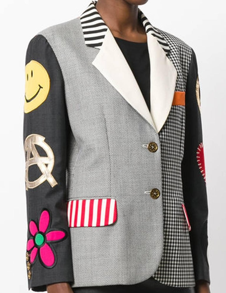 Moschino Couture black, white and multicolour wool embroidered multi panel jacket featuring notched lapels, a front button fastening, a chest pocket, front flap pockets, long sleeves, button cuffs, a striped print, a check pattern, a straight hem