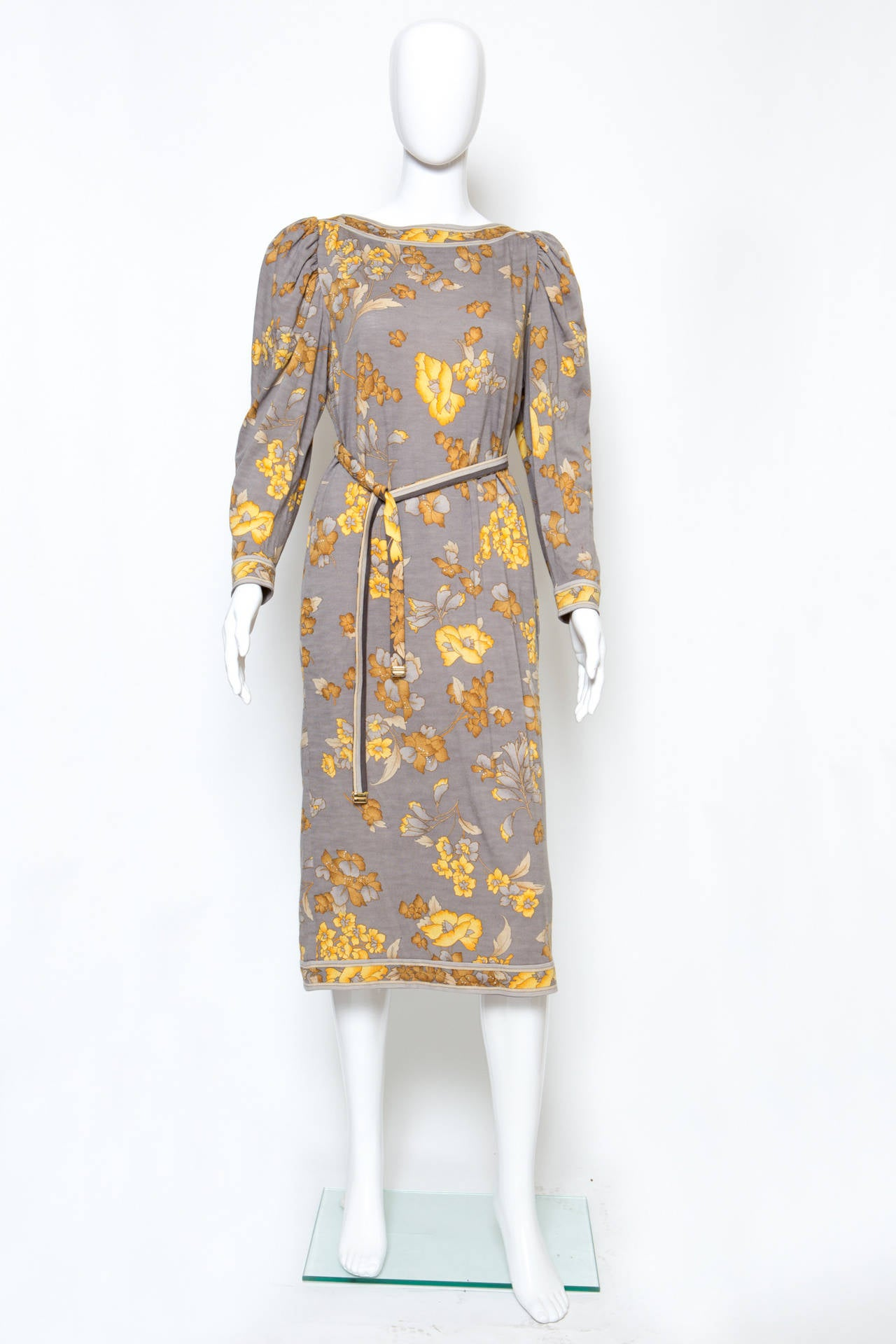 Amazing wool jersey dress from Leonard  featuring a flower print pattern in the ochre colors on a grey ground, long sleeves, flouncy top sleeves, side seams pockets, a seperated long belt with gold tone details edge with Leonard pitted on. The
