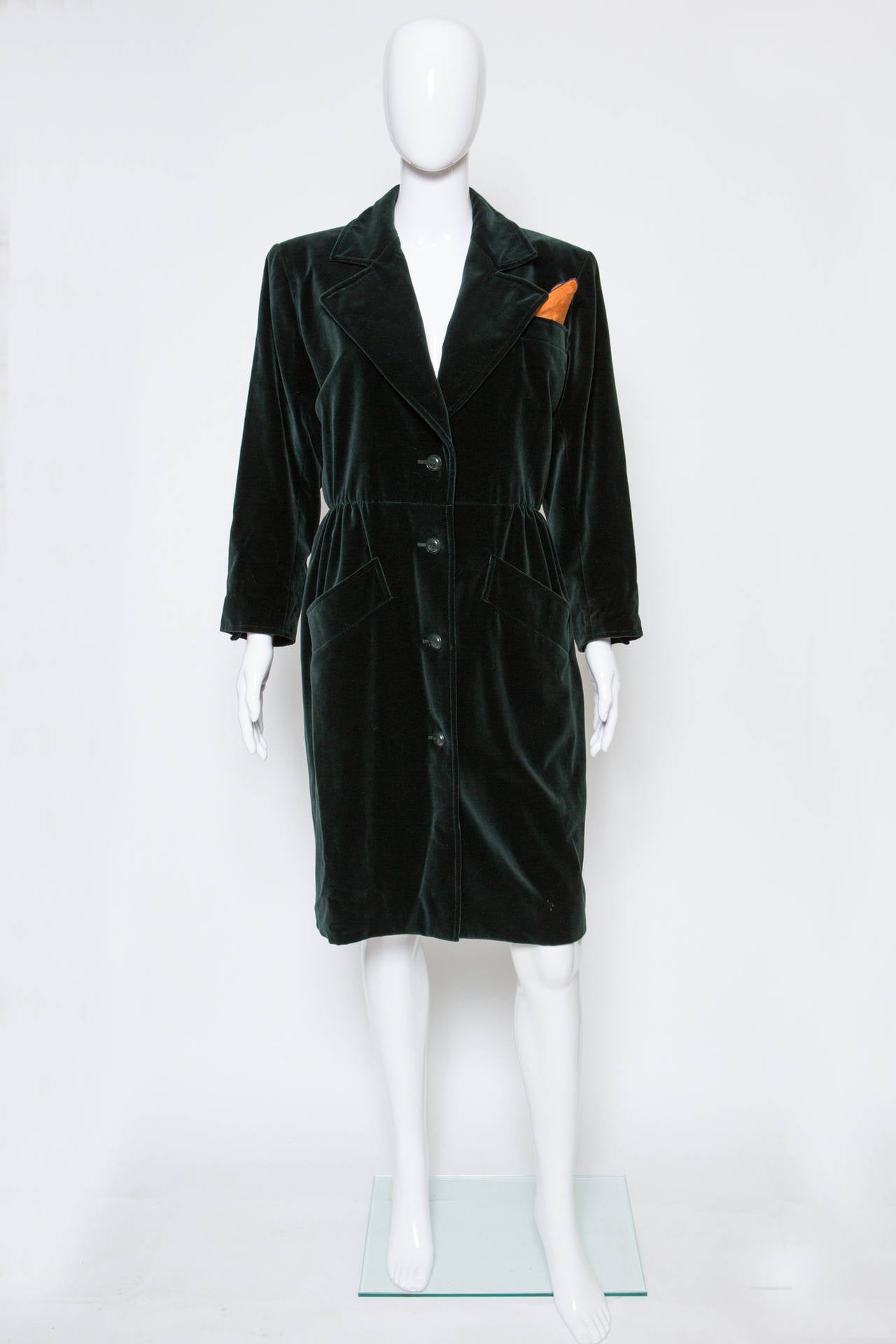 """1980s  Yves Saint Laurent dark green velvet coat, featuring a simple button opening, a fitted waist,it could be wear as a dress/coat, it gets shoulder pads with an across shoulder: 41cm. The coat gets a  YSL silk"""" pochette"""" in the bust"""