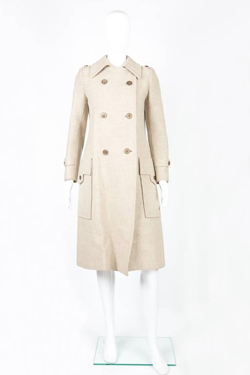 1960s Ted Lapidus ivory wool coat featuring a double breast opening, large patched pockets with side enter, shoulder straps, center back slit.  In good vintage condition. Made in France. Chest 36,2 in. ( 92 cm) Waist 35,4 in. ( 90 cm) Length