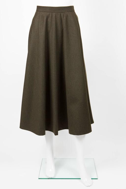Saint Laurent khaki large wool skirt featuring a fitted waistband, a large volume in bias, side seams pockets, side button and zip opening.100% wool. In excellent vintage condition. Made in France. Estimated size: We guarantee you will receive