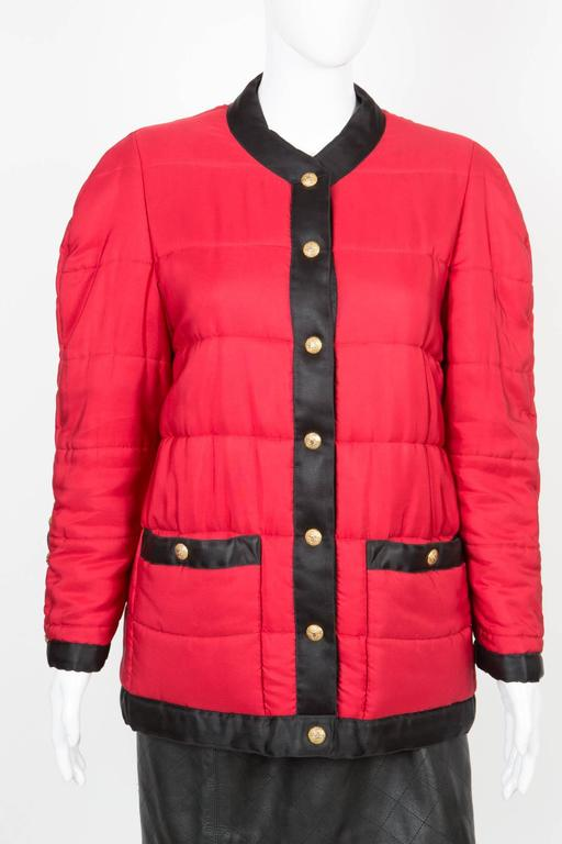 Chanel red padded silk coat featuring a black silk contrasted finishing, Gold tone logo snaps buttons, a black silk lining.See photo in Chanel Publicity .. 100% silk  In excellent vintage condition.  Made in France. We guarantee you will receive