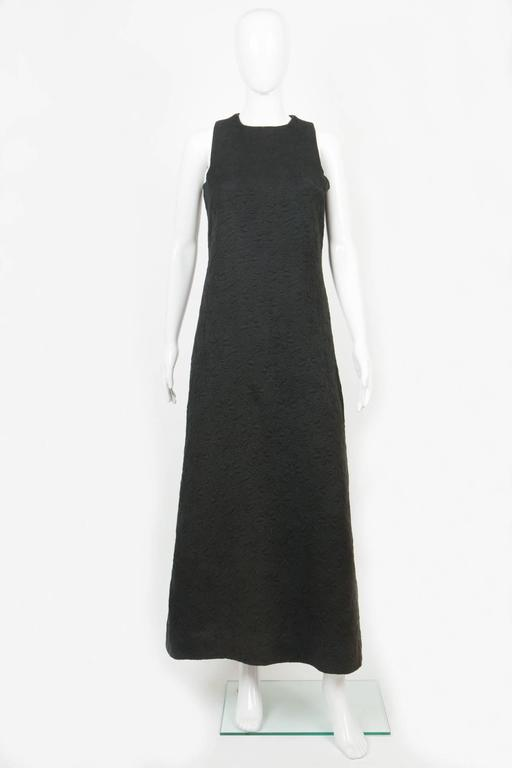 1960s rare black cocktail dress Miss Dior by Marc Bohan featuring a cotton jacquard fabric pattern, recovered center back button opening, square armhole details. silk camel lining. In excellent outside vintage condition, the black top as done some