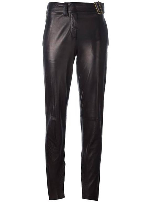 Black metallic lambskin trousers Yves Saint Laurent featuring a high rise, a lambskin belt with a side buckle, a tapered leg and gold-tone hook details at legs bottoms.
