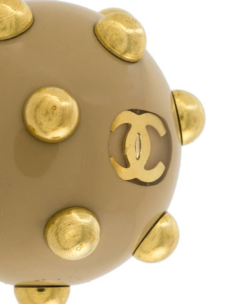 2000s Chanel camel toned resin embellished clip-on earrings featuring rounded stud embellishments, a signature interlocking CC logo and gold-tone hardware.   Chanel signature plaque on the reverse of the earrings .  Length: 0,8in. (2cm) X 0,8in.