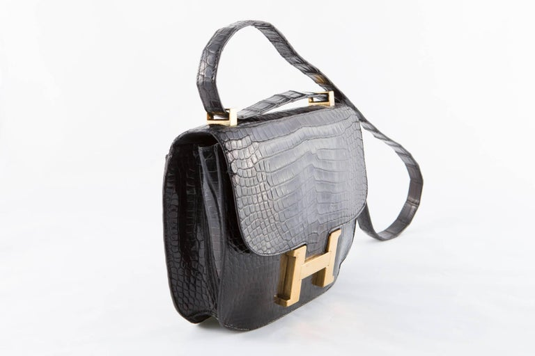 1960s Black crocodile leather Hermes Constance  shoulder bag featuring a shoulder strap, front gold plated H closure, inside in lamb leather snap pocket and compartments, gold-tone hardware, an inside logo stamp Hermes Paris Made in France. In