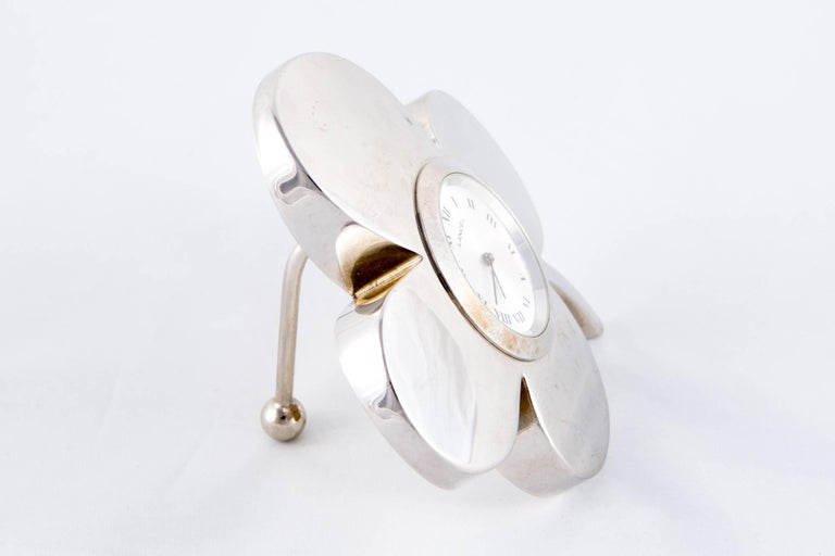 1970s rare Lancel clock featuring a silver tone flower shape, a back foot support.  In excellent vintage condition. Made in France. Maximum Length: 3.5in. (9cm) Maximum width: 3.5in. (9cm) We guarantee you will receive this gorgeous item as