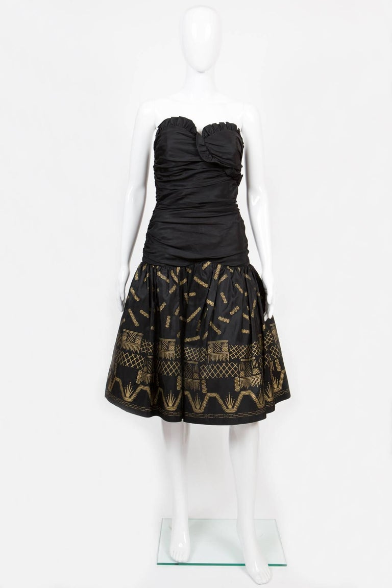 1980s gorgeous Zandra Rhodes evening dress featuring a silk black taffeta fabric base, with gold metallic paint on the skirt portion, skirt gets an inside a tulle petticoat, a center back zip opening, the top edge is ruffled and cuts through the