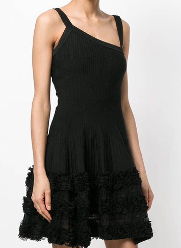 Azzedine Alaia black silk asymmetric mini dress dress featuring an asymmetric neckline, spaghetti straps, a fitted waist, a flared skirt, lace panels, a ruffle trimming, a ribbed design, a short length and an invisible back zip fastening. In