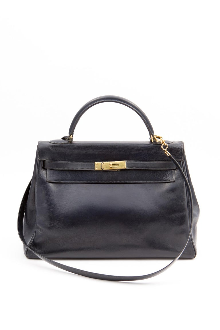 1960-1970s Hermès dark navy box calf leather Kelly tote bag 32cm featuring foldover top with twist-lock closure, a top handle, a trapeze body, plated-gold hardware, an internal slip pocket, a clochette, and a detachable box calf shoulder strap