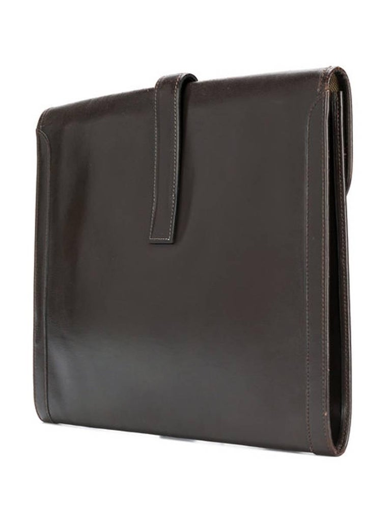 Hermès large Jigé chocolate box leather clutch featuring a foldover top, a strap closure, a front logo patch, a cotton canvas lining, a center front Hermes Paris stamp.  In excellent vintage condition. Made in France. Width: 13.4 in. (34cm) Height: