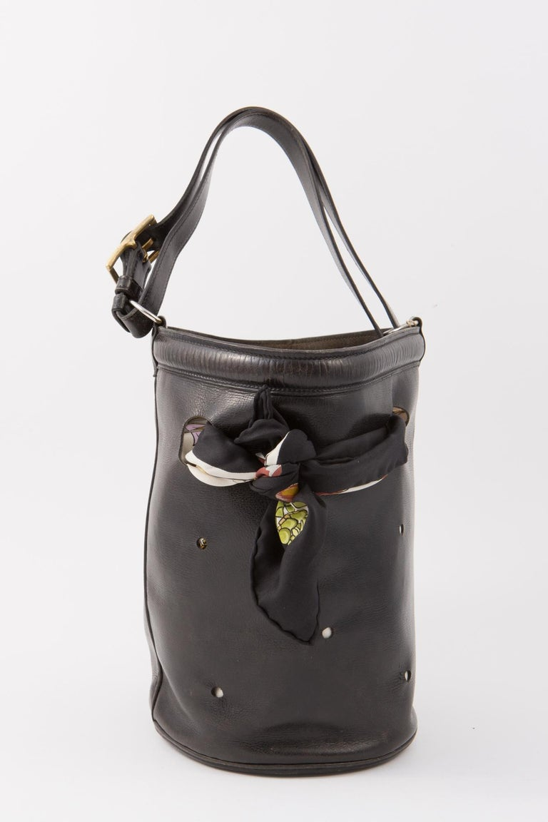 1950s Hermès black box calf leather Mangeoire tote bag featuring a top handle, plated gold-tone hardware, rounds in cutwork to pass a scarf in, no lining, a bottom Hermes Paris stamp.  We deliver it with an Hermès Passementerie silk scarf (35 in.