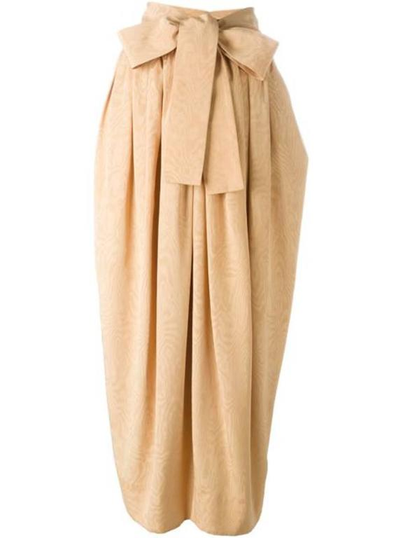 Exceptionally apricot soft iridescent watered moire silk maxi long skirt from Saint-Laurent featuring a lond detachable belt to do a long bow, pleats at waist, side pockets, and a side zip fastening.