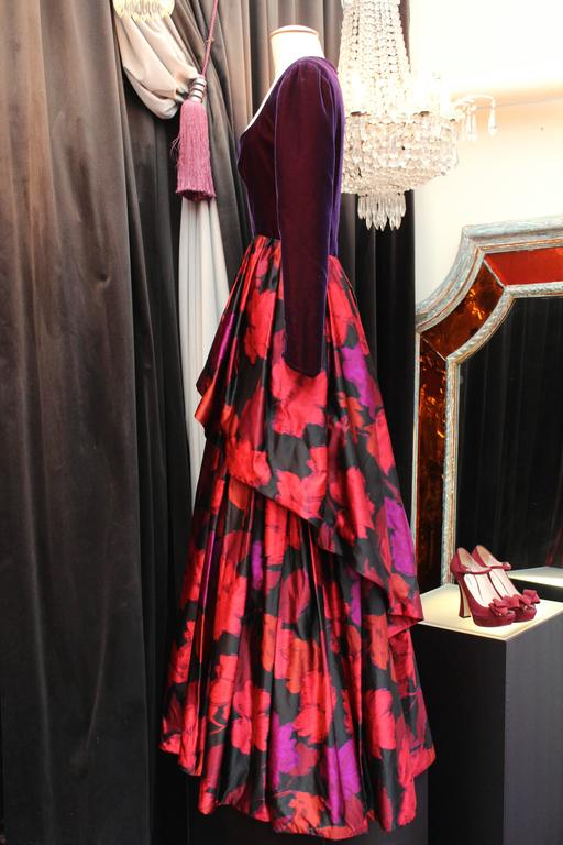 LAPIDUS HAUTE COUTURE (Paris) Evening gown composed of a long sleeves top in velvet plum color and a long printed silk taffeta skirt with a plum, red and fuchsia floral motif.  The magnificient flared skirt, longer at the rear, is constructed with