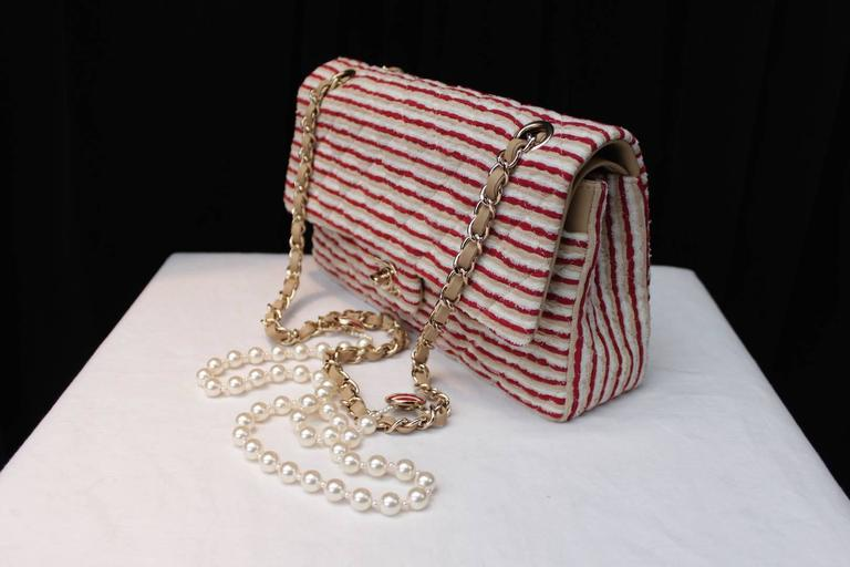 CHANEL (Made in Italy) Timeless model bag consisting of thin stripes of red and ecru cotton and white lace displayed in a pattern of horizontal stripes.   Gilt metal hardaware including a CC turnlock clasp and a sliding chain handle interlaced
