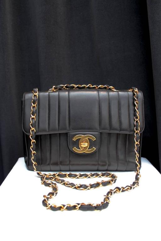 CHANEL. Large black leather bag (close to Jumbo size) with a wide flap, vertically striped with tone-on-tone stitching, and adorned with gilt metal hardware including a CC turnlock clasp and sliding chain interlaced with black leather strap.