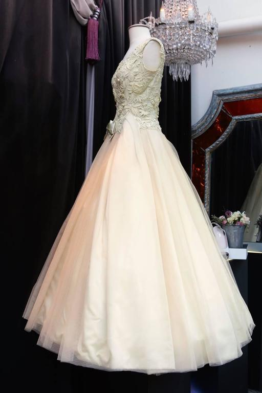 JEAN PATOU PARIS Lovely evening dress with large straps and bustier part covered with beige guipure featuring flowers.   The long and wide skirt part is composed of several layers of beige tulle on a yellow satin lining.   The dress is adorned on
