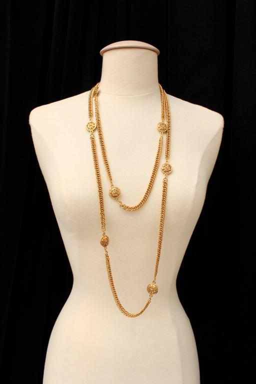 CHANEL (Made in France) Gilt metal long necklace composed of gilt chain alternated with round medals struck with the brand name and a lion silhouette.   The necklace is signed on plate, collection 2 cc 3 dating from the early 1990s.  Very good