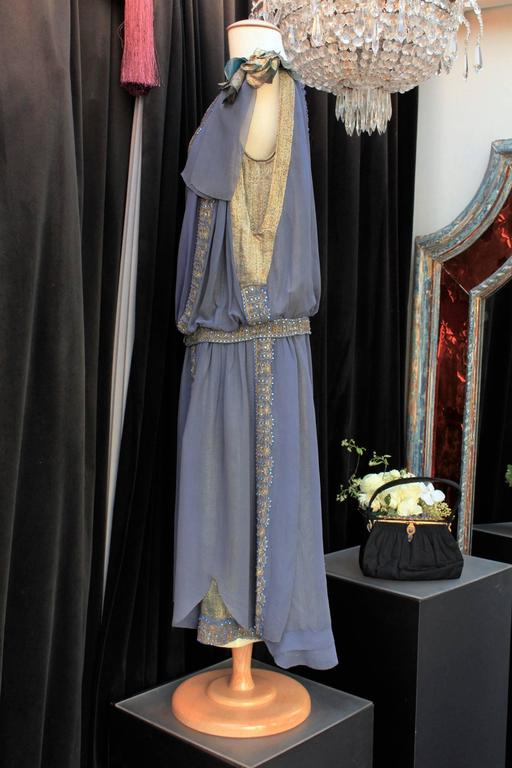 ANONYME Beautiful dress of the 1920s made of chiffons of blue night night embroidered with goldtone lame threads and blue beads and decorated with two flowers in fabric embroidered lamé thread.   The mid-length dress is constructed sleeveless, with