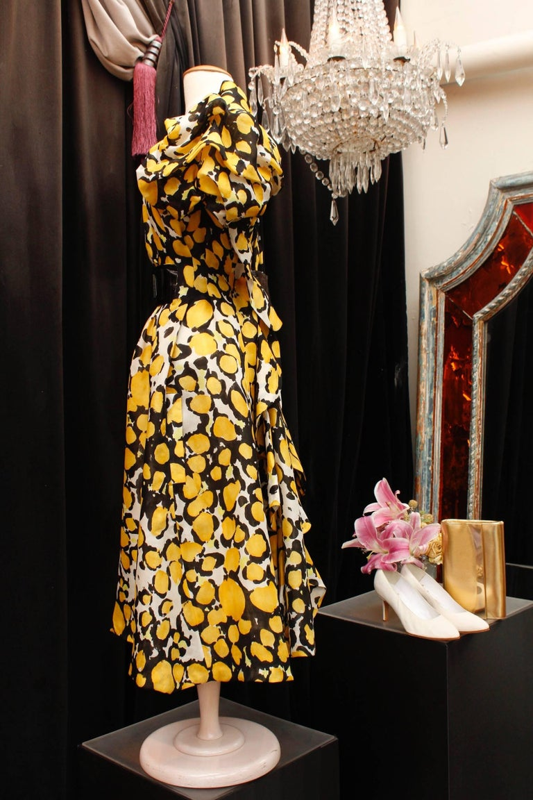 CHRISTIAN LACROIX (Made in France) - 1980/1990s - Long white organza dress with abstract floral pattern in yellow and black. The waist is emphasized by a wide reversible belt; one of its side is made of organza, the reverse of  black eel leather